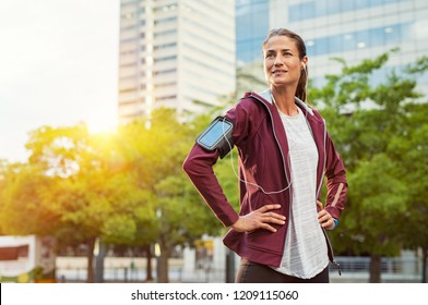 Proud woman listening music with earphones while standing and resting after running outdoors. Mature lady wearing jacket and standing after morning run in urban city. Satisfied runner looking away.