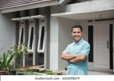 proud young asian man standing in front of his new house