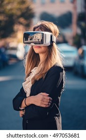 Proud young beautiful girl gesture testing virtual reality 3D video glasses VR headset dressed in a office outfit impressed by augmented reality on the street and beautiful autumn sun light colors
