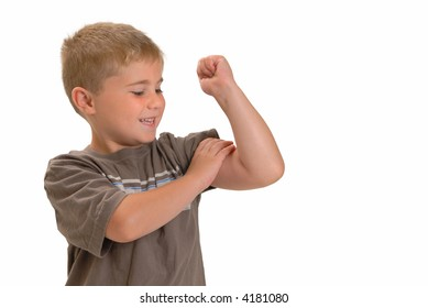 Proud young boy feeling his muscle on his arm, isolated on white