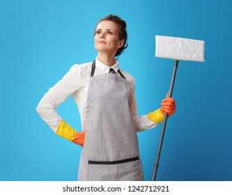 proud young housemaid in apron with a mop against blue background. Professional results by professional and regular woman cleaners