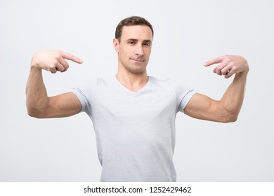 Proud young italian man in white t-shirt, standing, pointing himself and looking at camera with serious egoist face. Studio shoot
