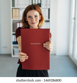 Proud young woman holding out her CV portfolio towards the camera with a pleased happy smile in a concept of human resources, job applications and employment. Bewerbung is german word for application