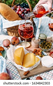 Provencal-style picnic with rose wine, croissants and cheese. Man pours wine into a glass. Wine is pouring from a bottle. Close-up