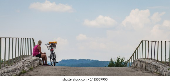 Provence / France - July 17, 2013  - Lady sitting next to her bike on a bridge while looking at the French Landscape