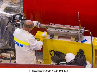 PROVENCE, FRANCE - JULY 31, 2017: Worker brushes weld in the ITER PF Coils Winding facility building, ITER, International Fusion Energy Organization.