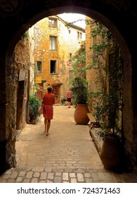 PROVENCE, FRANCE – JUNE 13, 2017: People explore a picturesque narrow street framed by an archway in the medieval Provencal village of Tourrettes-sur-Loup.