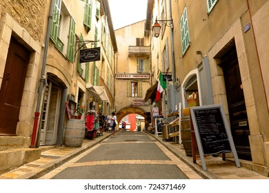 PROVENCE, FRANCE – JUNE 13, 2017: A woman browses a clothes rack in a narrow shop-lined street in the medieval Provencal village of Valbonne, France.