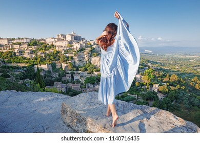 Provence, France. Young French lady dressing traditional Provencal apparel, enjoying the sunset at Gordes, Provence with incredible landscape panorama of valley and ancient hill top town Gordes.