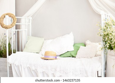 Provence, rustic style. White wall, retro bed, straw hat. Shabby chic Provencal style bedroom interior. Village, country house. A straw hat lies on a white bed in the morning. Bright bedroom interior