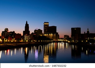 Providence, Rhode Island, USA - August 24, 2019 - Night Image of Downtown Skyline From The Providence River Pedestrian Bridge With Long Exposure, Blue Sky and Reflections In River.