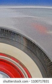 Providence, Rhode Island/USA- February 24, 2017: A vertical high definition closeup image of the white wall tire and red hubcap on a vintage Buick 8.