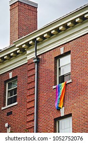 Providence, Rhode Island/USA- October 3, 2016: A vertical image of a diversity and equality flag hanging out of the top story of a brick building on an urban campus.