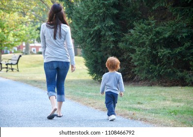 Providence, Rhode Island/USA- September 28, 2013: A horizontal image of an unidentified young woman and boy child walking down a paved path on an urban boulevard.