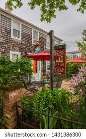"""Provincetown, MA - June 11, 2019: Rose and Crown Guest House was built in the 1780's in Georgian architectural style, and has a ship's figurehead """"Jane Elizabeth"""" above the front door."""