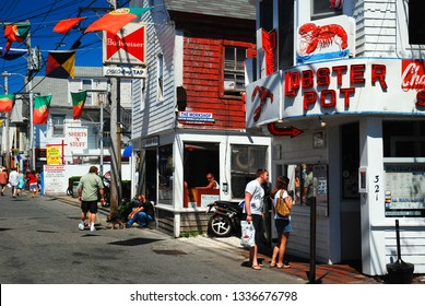 Provincetown, MA, USA July 5, 2009 A couple strolling on Commercial Street in downtown Provincetown, Cape Cod, Massachusetts, stops to read a menu at a local seafood restuarant