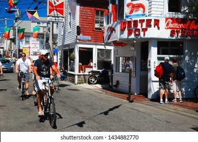 Provincetown, MA, USA July 5 2009 An adult man rides his bike down Commercial Street on a summer's day in Provicncetown, Cape Cod,. Massachusetts