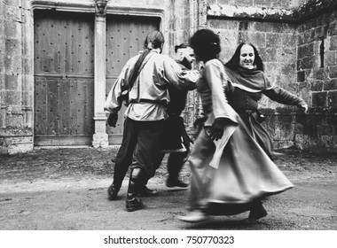 PROVINS, FRANCE - DECEMBER 11, 2016: People dancing in medieval costumes near the church during the traditional Christmas Medieval fair. Old town of Provins is UNESCO World Heritage Site.
