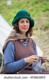 PROVINS, FRANCE - JUNE 12, 2016: Woman in medieval costume knitting pullover. The medieval festival is held annually in a weekend of June.