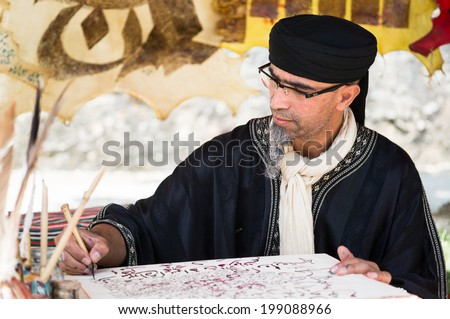 PROVINS, FRANCE - JUNE 15, 2014: Man in old Arabic costume writes on a parchment. The medieval festival is held annually in a weekend of June.