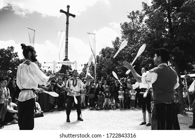 PROVINS, FRANCE - JUNE 16, 2019: Al Cantara street artists juggling with skittles for public during traditional Medieval festival. Provins town is UNESCO World Heritage Site. Black white photo.