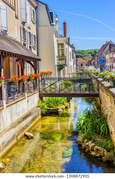 PROVINS, FRANCE - JUNE 4, 2015: Picturesque Narrow Street with a canal and flowers in medieval town of Provins. Provins - commune in Seine-et-Marne department, north-central France.