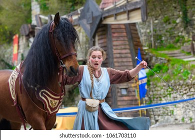 PROVINS, FRANCE - MARCH 31, 2018: Unidentified girl in blue dress plays with a horse in the medieval reconstruction of Legend of the Knights