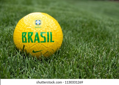Provo, UT, USA - 2 July 2018:  Yellow football with Brasil national team logo in the grass. Soccer ball of 5 time World Cup champions Brazil on a football pitch.