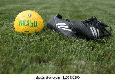 Provo, UT, USA - 2 July 2018: Brazil national football team soccer ball and soccer cleats on the grass. Brazil team football and football boots on the pitch.