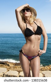 provocative blonde girl with sexy bikini, hat and sunglasses in summertime in sensual pose with sea on background