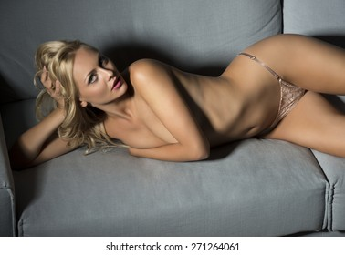 provocative blonde woman with charming expression posing with nude body and lace panties on sofa, covering her naked breast and looking in camera
