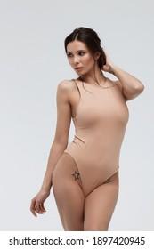 Provocative brunette woman in elegant tender beige lingerie looking at camera in studio