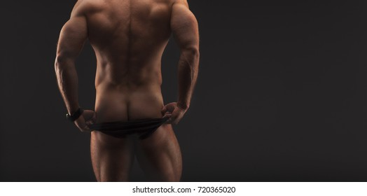 provocative faceless photo of a very muscular shirtless male model showing ass in black underwear against gray studio background