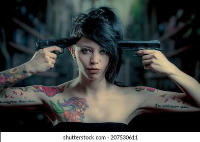 c90884101 provocative tattooed girl poiting guns to her head looking at camera