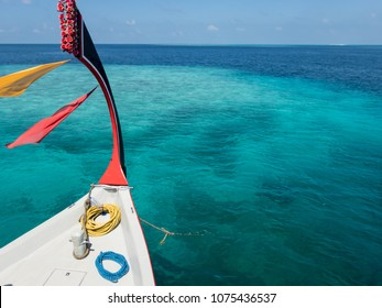Prow of colorful dhoni boat with prayer scarves and roses floating over coral reef