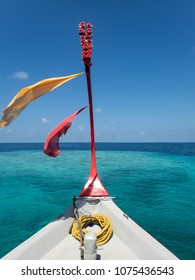 Prow of colorful dhoni boat with prayer scarves floating over coral reef