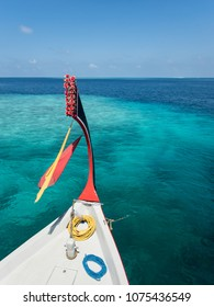 Prow of colorful red and white dhoni boat with prayer scarves floating over coral reef