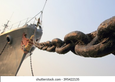 Prow old rusty grey military ship with the metallic anchor chain diagonally