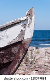 Prow of an old wooden boat with peeling flaking paint beached on a stony beach near the ocean