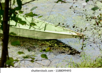 prow of traditional green metal boat moored in oxbow lake at Ticino river , shot in a bright cloudy fall day  in Ticino park near Bernate, Milan, Lombardy, Italy