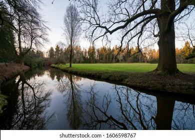 Pruhonice park around Pruhonice castle in winter. The Czech Republic, Europe. Landscape reflected in a pond.