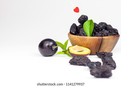Prune, dried plums fruits on white  background. Dry plums in a wooden bowl. Healthy fruit