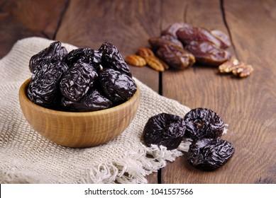 Prunes in a bowl on a dark wooden background.