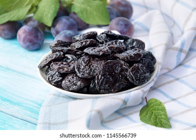 Prunes in a bowl on an old wooden table on a background of fresh plums. Prunes and fresh plums on the table.