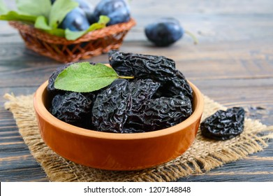 Prunes in a clay bowl and fresh plums, leaves on a wooden table. Fresh prunes for healthy life.