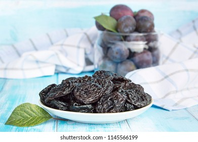 Prunes in a plate on an old light wooden table on a background of fresh plums. Background with prunes.
