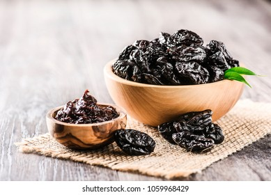 Prunes in wooden bowl and plum jam on old rustic table. dried plums on table. Heap of prunes on old board.