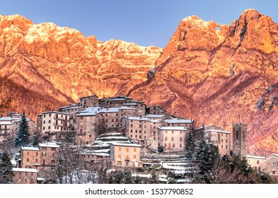 """Pruno little village in the apuan alps in tuscany, snowy day with beautiful golden sunset, on the right top view the famous """"monte forato"""", """"Holed Mountain"""", a natural hole formed by an arch."""