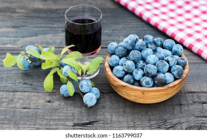 Prunus spinosa. Sloe fruits liquor. Blackthorn in a wooden bowl on the dark wooden background.