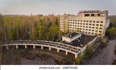 Prypiat, Ukraine, 5th may, 2019. Depressing bird`s eye view of a ghost concrete hotel with its ruined parking lot and rusty shops nearby, in mutant forest  in Prypiat in spring.